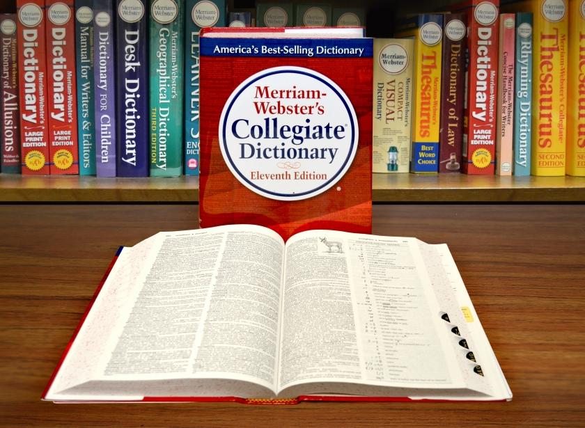 Merriam-Webster szótárak egy polcon, előttük a Collegiate Dictionary borítója, és egy közepén kinyitva lefektetett példány