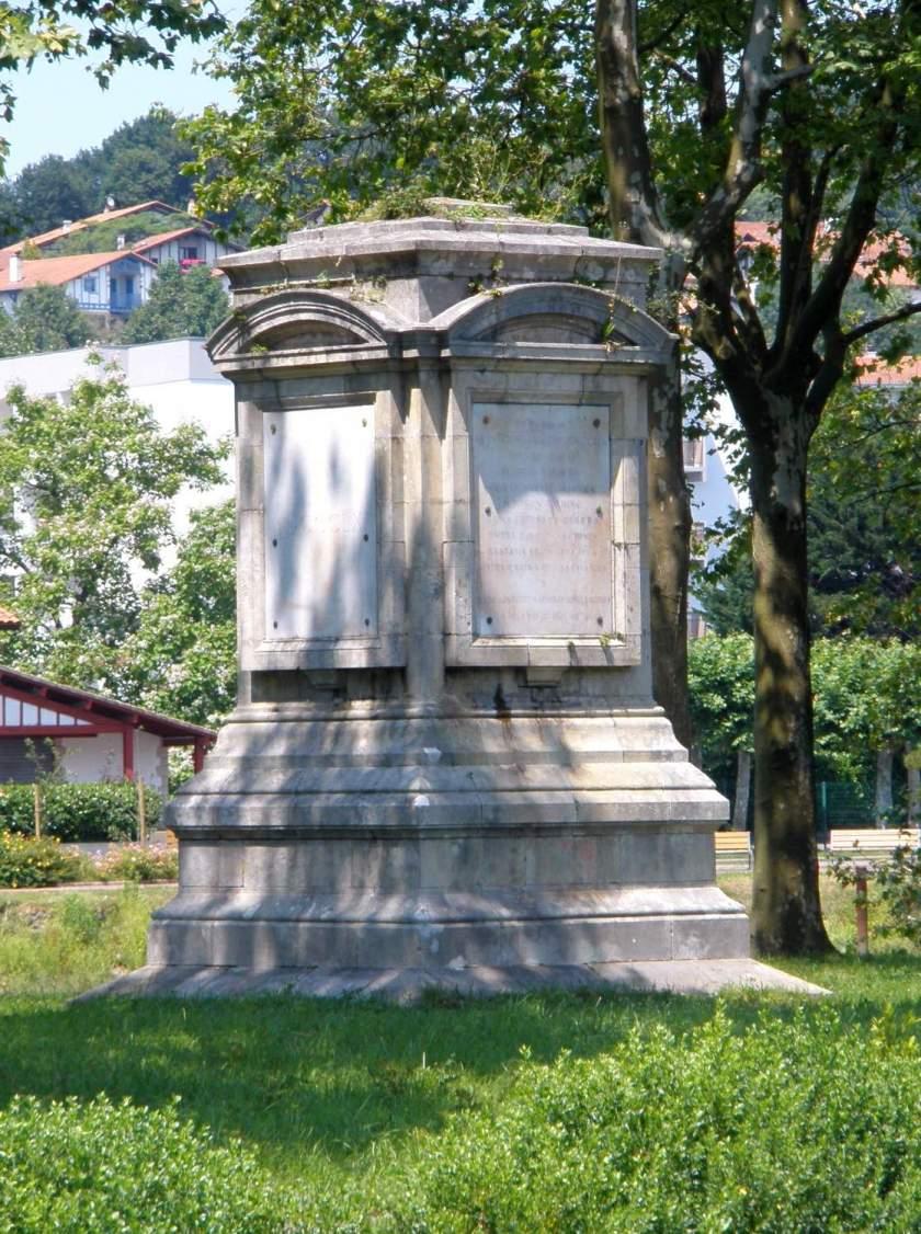 Alacsony, fehér, neoreneszánsz emlékoszlop négy oldalán feliratos táblával, a pireneusi békekötés emlékére