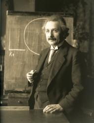 Albert Einstein egy tábla előtt állva, kezét az előtte lévő asztalon nyugtatja, másik kezében krétát tart és derűsen elnéz a bal oldalunk mellett.